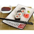 Sushi served on white plate — Stock Photo