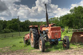 Old red tractor under a stormy sky — Stock Photo