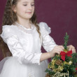 Girl decorates a merry christmas tree — Stock Photo