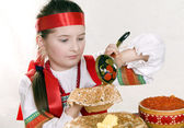 Russian girl behind a table with pancakes — Stock Photo