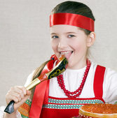 Girl licks a spoon with red caviar — Stock Photo