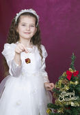Girl decorates christmas tree — Stock Photo