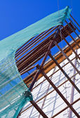 Rusted scaffold with green protection mesh. — Stock Photo