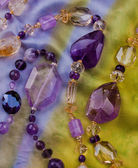 Beautiful necklace of big violet and yellow amethysts laid on bright multic — Stock Photo