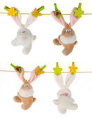 Four plush toy rabbits hanging on rope — Stock Photo