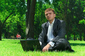 Businessman in a park on the grass wiht laptop — Stock Photo