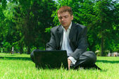 Businessman in a park on the grass workin on laptop — Stock Photo