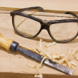 Protective glasses and chisel on wood table — Stock Photo