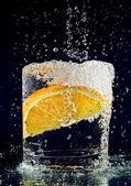 Plátek pomeranče padají ve sklenici s vodou na temně modré