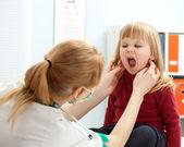 Lékař pediatr vyšetřující dětská ústa