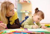 Učitel s dítětem v mateřské školce