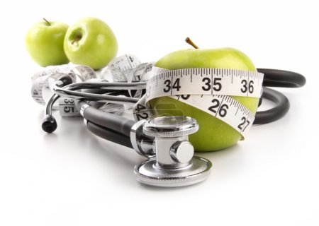 Green apples with stethoscope against white
