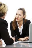 Dvě ženy během obchodního jednání s notebookem na bílém pozadí studio