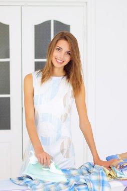 Beautiful girl next to ironing board