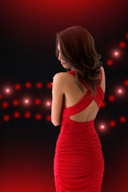 Elegant girl in a red dress on a black background with the light