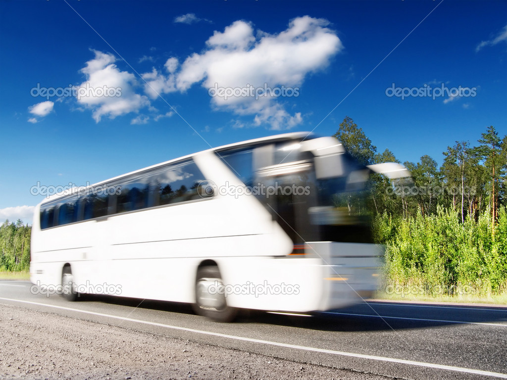 White bus speeding on highway, blurred in motion