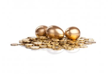 Three golden eggs on coins isolated on white