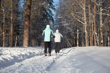 Man and woman walk on ski in winter forest