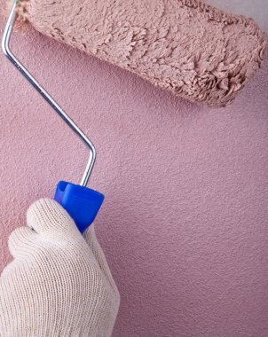 House painter using a paint roller, painting a wall in motion