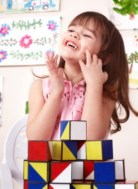 Child playing block in play room.