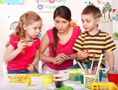 Children with teacher painting in play room.