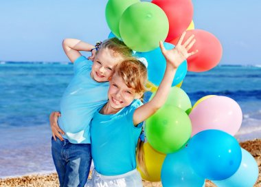 Children playing with balloons at the beach