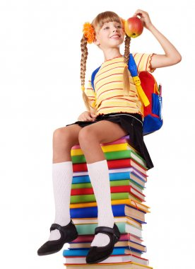 Schoolgirl sitting on pile of books.