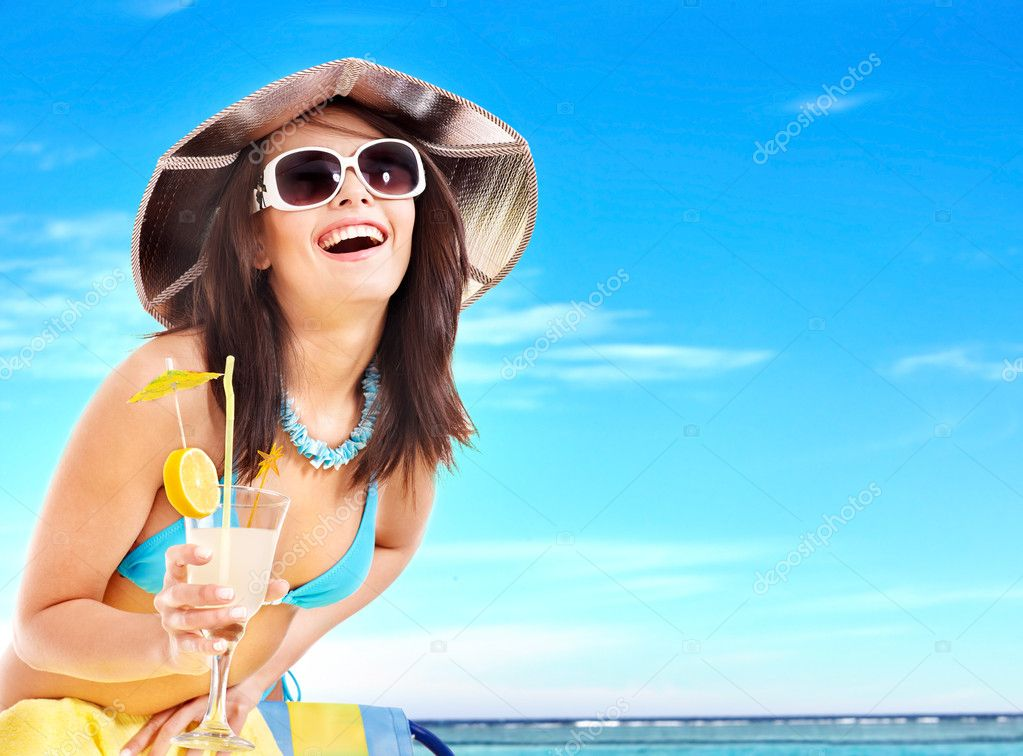 Girl in bikini drinking cocktail.