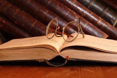 Vintage still life with very old eyeglasses lying on open book near bookshelf stock vector