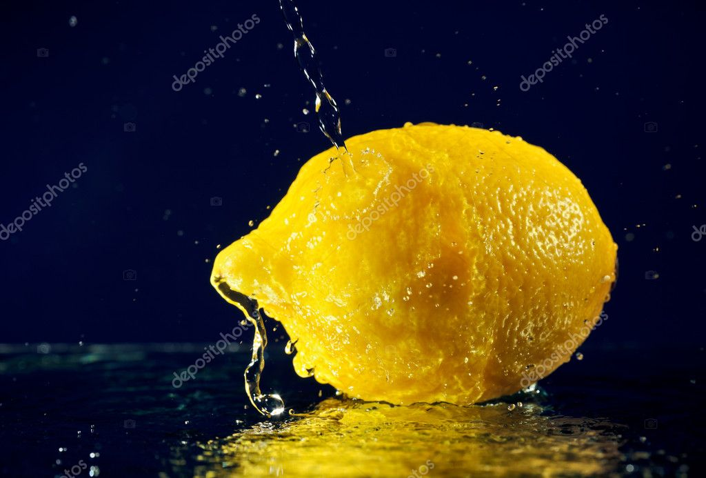Whole lemon with stopped motion water drops on deep blue