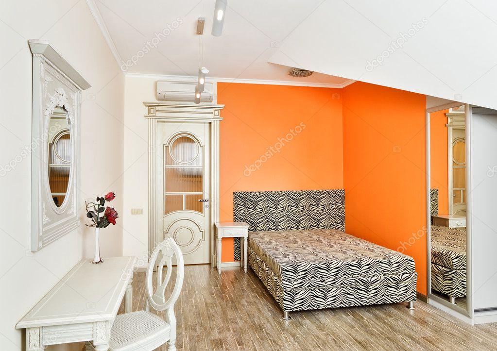 Moderne slaapkamer in heldere oranje kleuren met zebra patroon bed