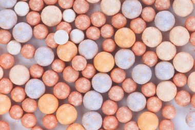 Beige cosmetics multicolor rouge balls background, macro view