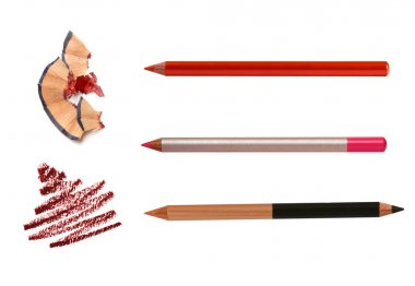 Cosmetic pencils sharpening with husk on white and stroke sample
