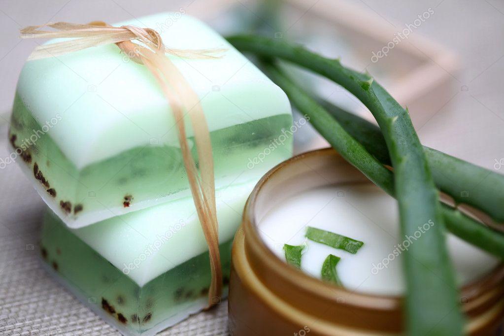 Handmade soap bars, aloe, vera leaves and moisturizer.