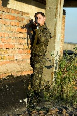 Sniper in camouflage ambushing behind brick wall stock vector