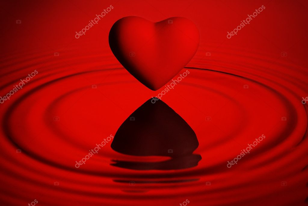 Red heart over water ripples