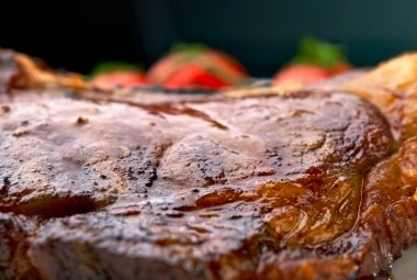 Macro of grilled meat ribs on white plate with tomatoes