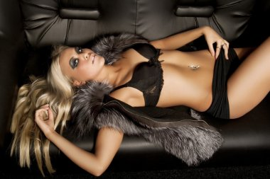 Model dressed in fur laying on sofa