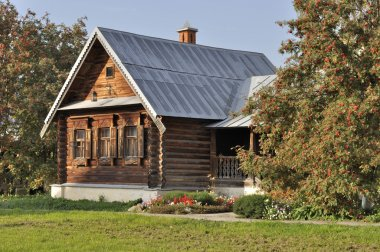 Beautiful wooden house with porch, flower bed and rowan-trees