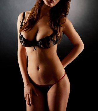 Girl in lingerie over dark background