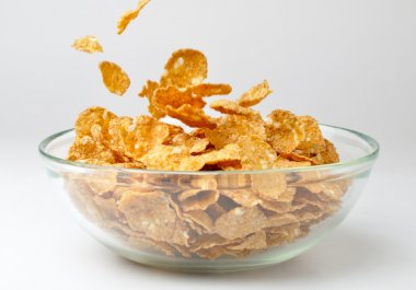 Closeup of a bowl with pouring cereal flakes
