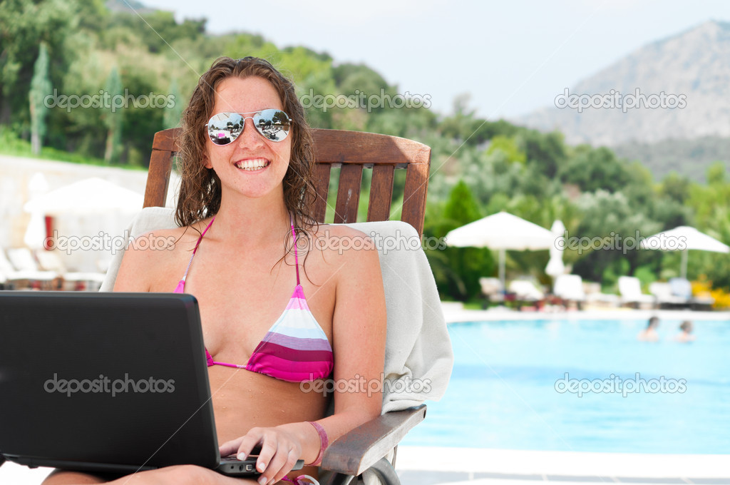 Woman with laptop near pool