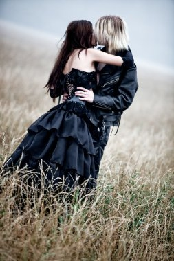 Young goth couple kissing outdoors