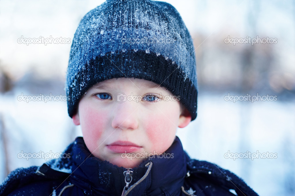 The sad crying boy with blue eyes in winter clothes