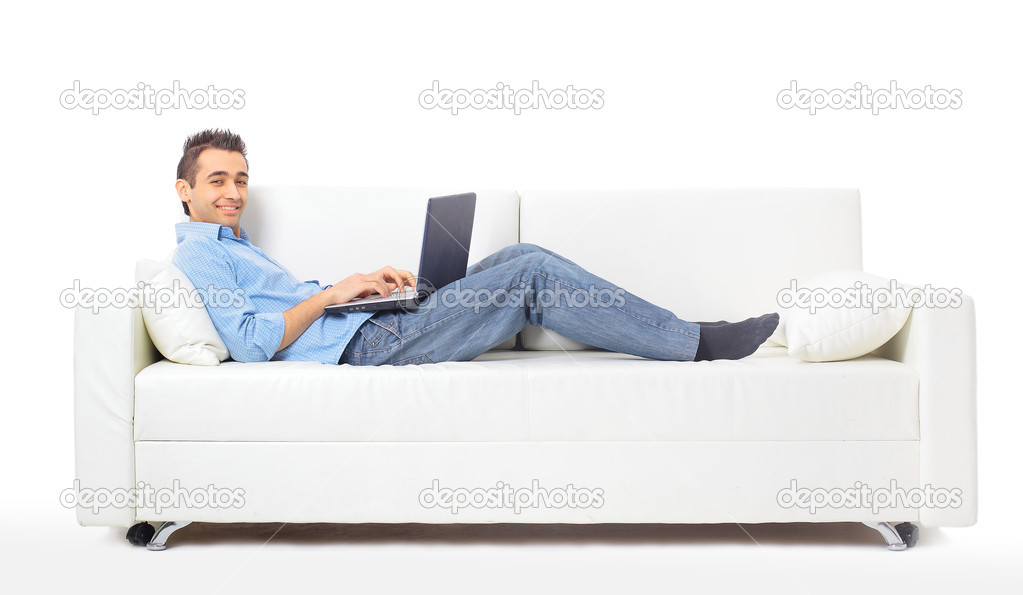 Happy man working on his laptop on the sofa at home