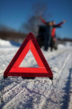 Man And Woman Broken Down On Country Road With Hazard Warning Sign In Foreg