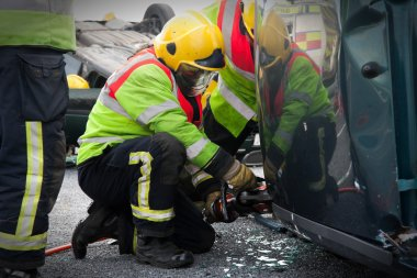 Fireman with Power Wedge at car crash