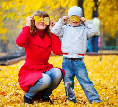 Child and mother with autumn leaves