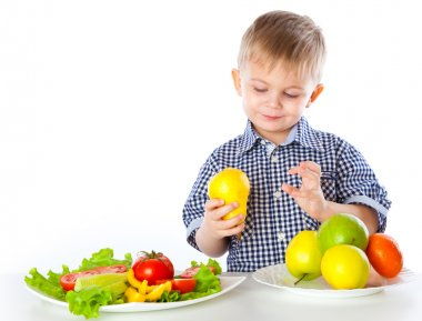 A boy and plates of vegetables and fruit