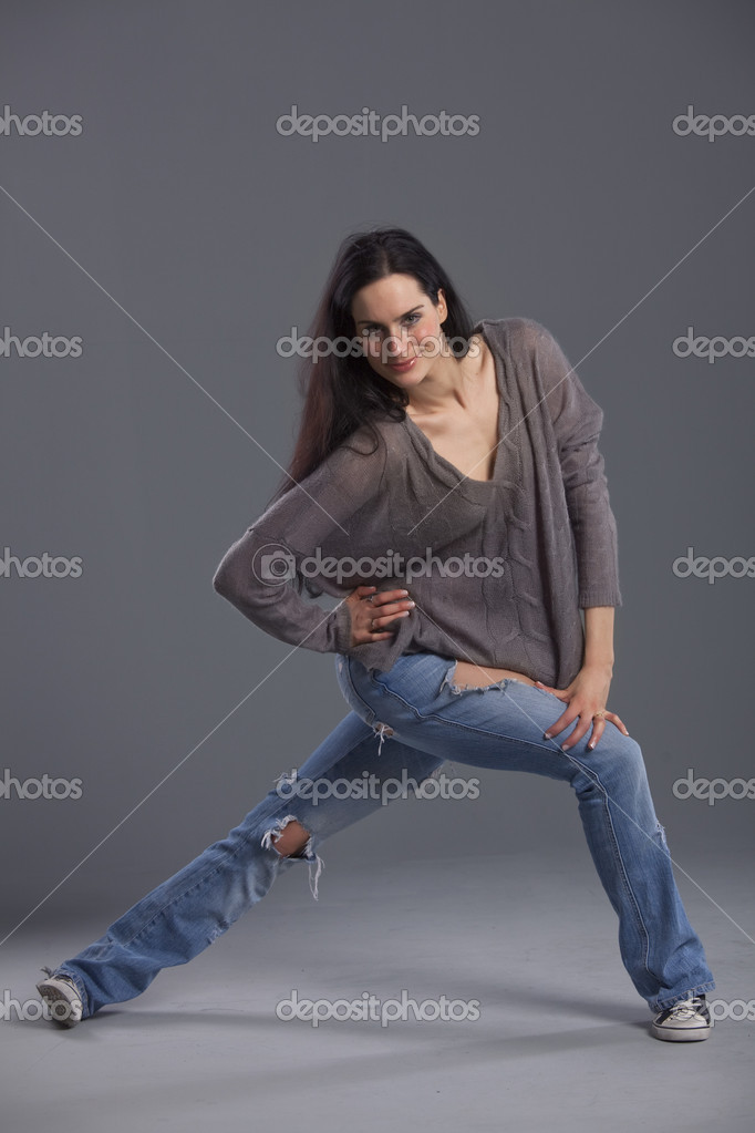Portrait of woman dancer in denim jeans over grey background
